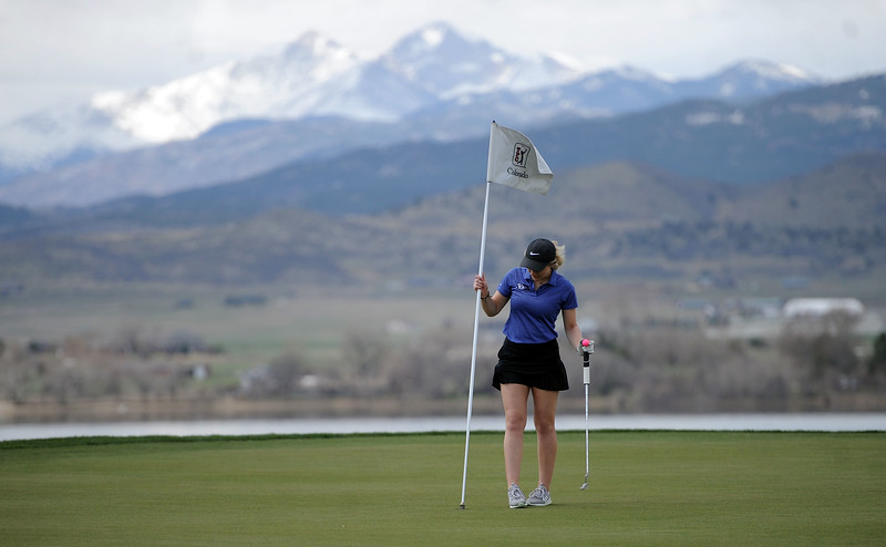 Resurrection Christian's Lindy Hekowczyk puts the flag in the 10th hole at TPC Colorado on April 15, 2019. (Colin Barnard/Loveland Reporter-Herald)