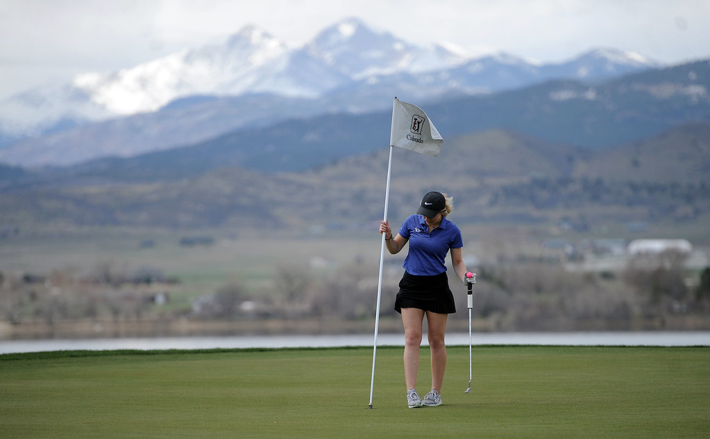 . Resurrection Christian\'s Lindy Hekowczyk puts the flag in the 10th hole at TPC Colorado on April 15, 2019. (Colin Barnard/Loveland Reporter-Herald)