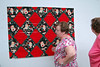 Lynn and Kathryn are checking out Cindy S. vintage Santa blocks on the design wall<br /> Sew cute!