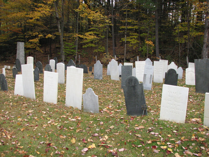 Putman's gravestone is the dark one just to the right of center in the front row in this photo. As you walk past the meetinghouse and enter the cemetery, you will find the grave in the left section of the cemetery, in the fourth row from the back, third stone from the dirt road separating the two sections.