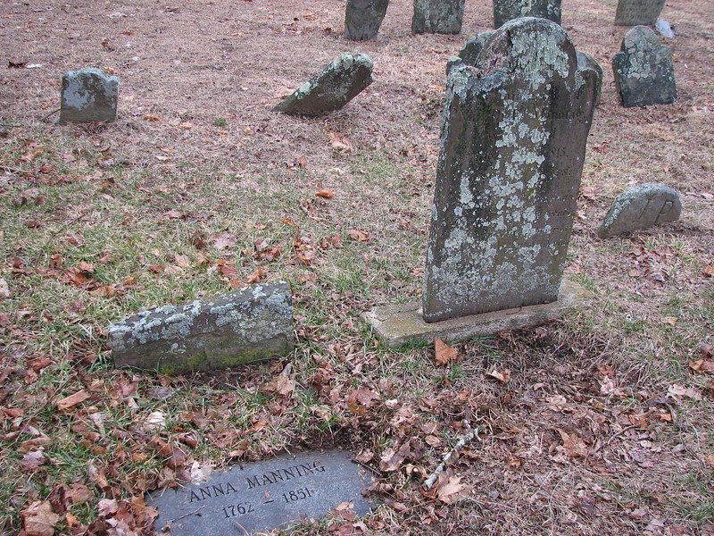 The gravestones of Diah Manning (the standing stone on the right) and his wife Anna (the flat stone in front of a broken stub.) The plot is situated two rows behind, and two to the left of the grave of Hannah Arnold, Benedict's mother (which is distinguished by a plaque on a post.)