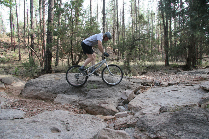 Swinging the rear wheel up to catch the rock face.