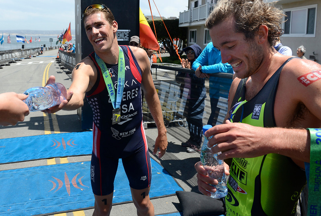 . Tommy Zaferes, left, of Aptos grabs a water beside Davide Giardini of Italy after winning the Mens Elite Race during the Triathlon at Pacific Grove on Saturday June 11, 2016. Giardini placed second. (David Royal - Monterey Herald)