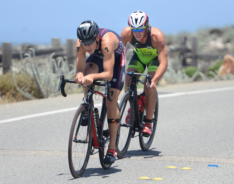 . Tommy Zaferes, left, of Aptos leads Davide Giardini of Italy as they ride near Asilomar State Park during the biking leg of the Mens Elite Race during the Triathlon at Pacific Grove on Saturday June 11, 2016. Zaferes won the race, Giardini placed second. (David Royal - Monterey Herald)