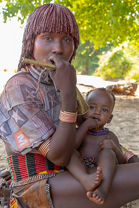 The mothers with children were quite devoted.  They are famous for their hairstyle using red clay