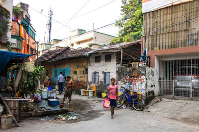 Typical neighborhood street scene: throughfare, auto storage, commerce, bath-house and garbage bin.