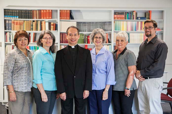 The diocesan Tribunal  staff includes (from left to right) Patricia Aragon; Anna Marie Chamblee, JCL; Fr. Anh Tran, JCL; Linda McKinney; JoAnn Gordon; and Carlos Sacasa, JCL. (Photo by Juan Guajardo / NTC)