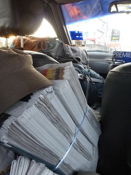 Sharing Our Taxi With Stacks of Newspapers