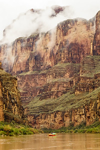A group of rafters floating past on a rainy day in the lower parts of the Grand Canyon.