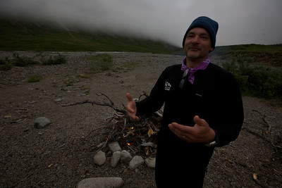 Chef in low light, low clouds, decade + old fire pit (we actually detest fire pits and always remove them in the wilderness), and pleasant bourbon glow, along the upper Kijik River - Lake Clark National Park.