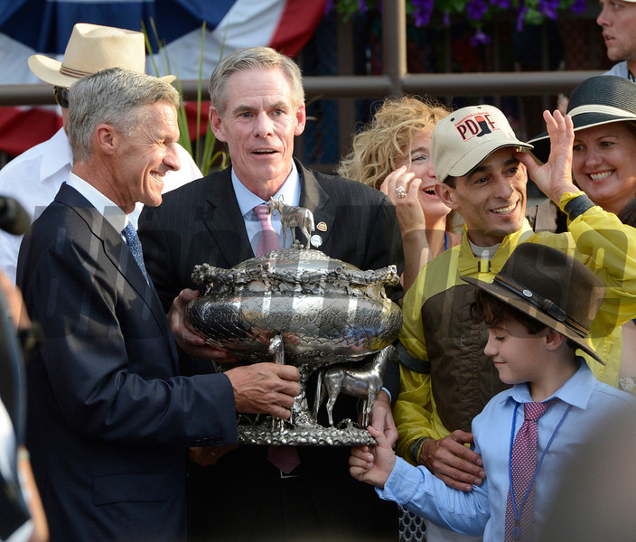 Union Rags's trainer Michael Matz, left and jockey John Velazquez, right receive the winner's trophy from NYRA Board Chairman Steve Dunker after Union Rags won the 144th running of The Belmont Stakes at Belmont Park in Elmont, N.Y. June 9, 2012.  Young Michael Velazquez, right holds the trophy as well.<br /> Photo by Skip Dickstein