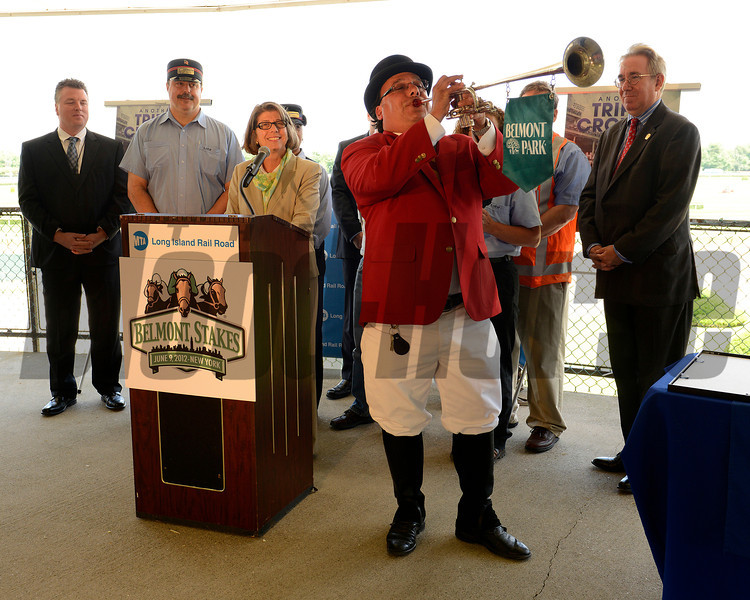 "Caption:  Sammy the Bugler plays ""call to Post"" outside the Long Island Railroad station entrance at Belmont Park as LIRR president Helena Williams (at podium) and others (including NY State Racing and Wagering Board exec John Sabini) look on.<br /> Belmont Park, June 7, 2012, Elmont, N.Y.<br /> Training hours activity on the track and at the barn.<br /> Photo by Anne M. Eberhardt"