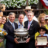 Trainer Michael Matz holds the August Belmont Trophy with John Velazquez off to the side.  Belmont Stakes, Belmont Park, 6/9/12.<br /> Photo by Steve Heuertz