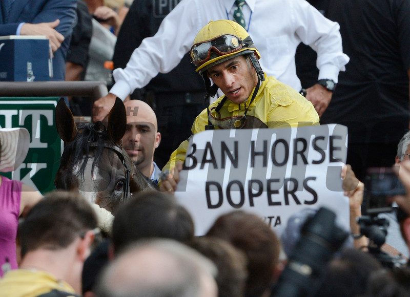 Jockey John Velazquez atop Union Rags is confronted by a PETA protestor in the winner's circle after he won the 144th running of The Belmont Stakes on Union Rags at Belmont Park in Elmont, N.Y. June 9, 2012.  <br /> Photo by Skip Dickstein