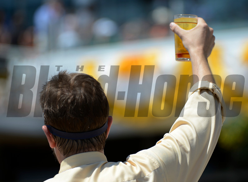 A Black-Eyed Susan salesman raises a glass on Preakness Day at Pimlico Race Course in Baltimore, MD May 19, 2012.  Photo by Skip Dickstein
