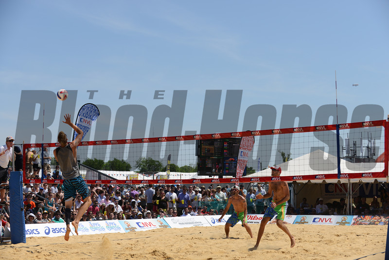 Casey Patterson goes up for a spike against Todd Rogers and Phil Dalhausser at the NVL final tournament game in the 2012 Preakness infield