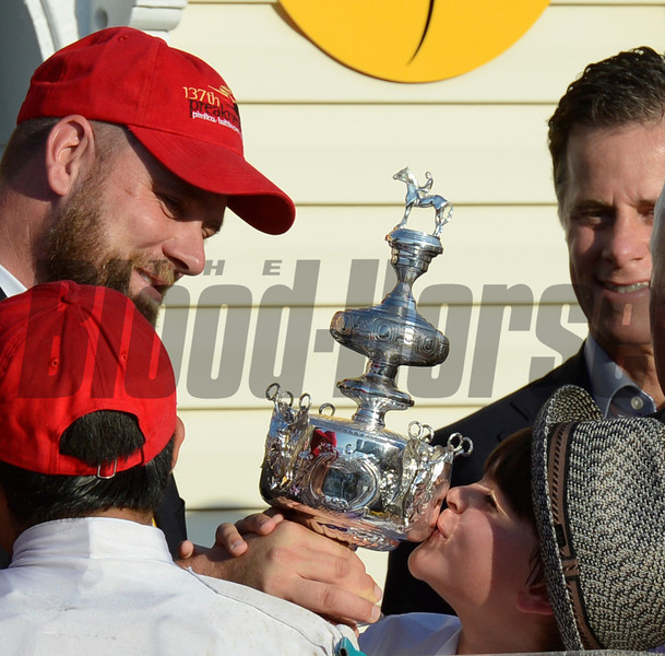Doug O'Neill, left holds shares the winner's trophy with a youngster after his trainee I'll Have Another won the 137th running of The Preakness Stakes at Pimlico in Baltimore, MD. May 19, 2012.    Skip Dickstein Photo