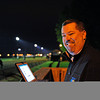 Caption:  Darren Rogers, in charge of Churchill media, uses his iPad and works from a stand in the barn area overlooking the track works.<br /> works and scenes at Churchill Downs near Louisville, Ky. on April 27, 2013, during Kentucky Derby and Kentucky Oaks week.<br /> 3Works4_27_13 image615<br /> Photo by Anne M. Eberhardt