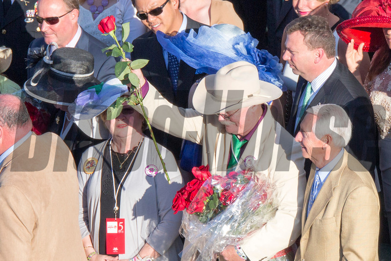 Steve Coburn takes a rose out to give to his wife in the winners circle after California Chrome with Victor Espinoza up wins the 140th running of the Kentucky Derby at Churchill Downs May 3, 2014. Photo by Mark Mahan