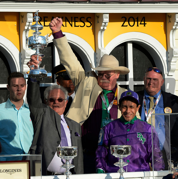 Trainer Art Sherman, left raises the winner's trophy aloft as owner Steven Coburn, center and jockey Victor Espinoza join in the celebration after California Chrome won the second leg of thoroughbred racing's Triple Crown with his win/ Times Union)