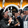 Trainer Keith Desormeaux kisses the winner's trophy as other owners Sol Kumin center and Matt Bryan look on after Exaggerator won the 141st runnoing of the Preakness Stakes.  Photo by Skip Dickstein