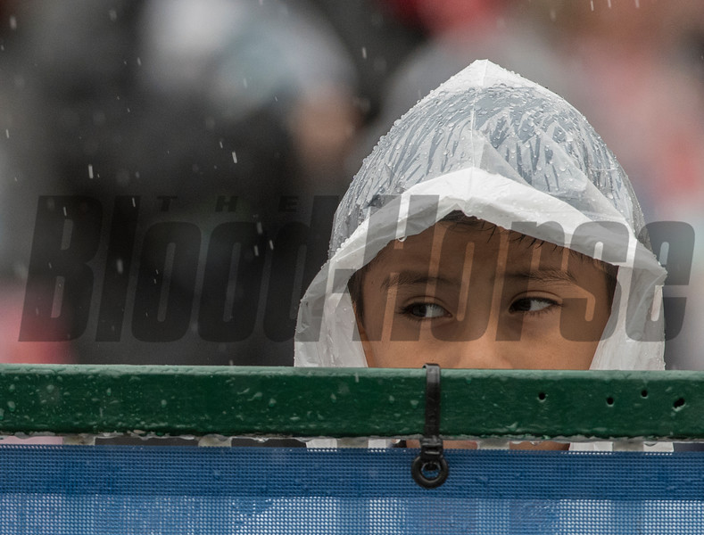 This young race fan watches the drops of water due to heavy rain at Churchill Downs on Kentucky Derby Day 144 Saturday May 5, 2018 in Louisville, Kentucky.  Photo by Skip Dickstein