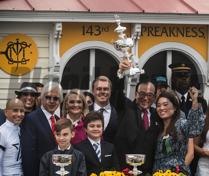 Two Ah Khing holds the winner's trophy aloft after Justify wins the 143rd running of the Preakness Stakes. Photo by Skip Dickstein