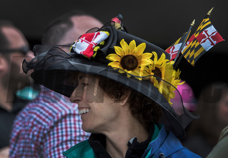A patron shows off her loyalty to Maryland with a hat full of flowers and flags on Preakness Day at Pimlico Race Course Saturday May 19, 2018.  Photo by Skip Dickstein