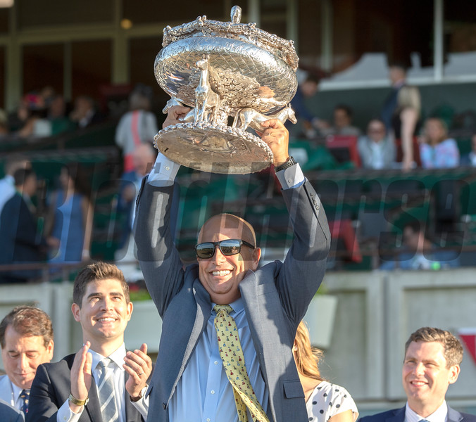 Trainer Mark Casse hoists the winner's trophy up after Sir Winston won the 151st running of the Belmont Stakes held Saturday June 8, 2019 at Belmont Park in Elmont, N.Y.  Photo by Skip Dickstein