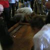 Jerusalem:  Church of the Holy Sepulcher; pilgrims kissing the plank on which Christ's body was washed