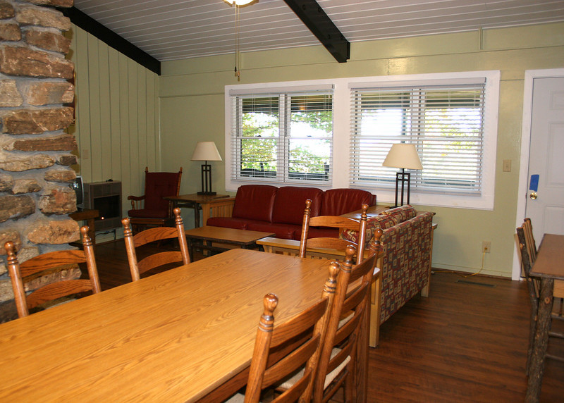 The dining room and living room in the cabin with the deck and view out the windows