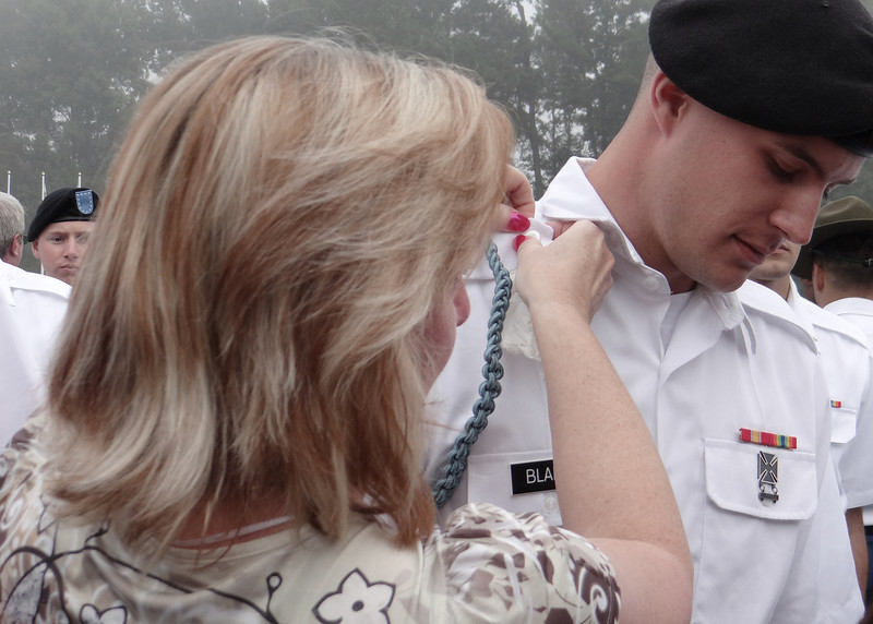 Proud mama, Donna, putting the blue cord on Travis.