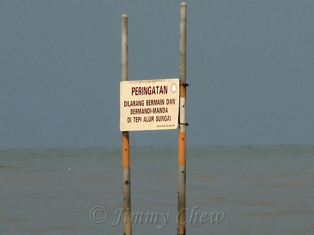 Warning notice to swimmers that beyond the poles is a river.