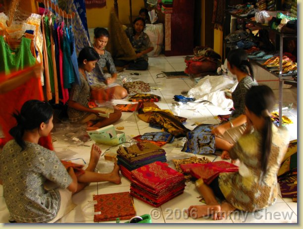 Workers sorting out the batiks in shop.