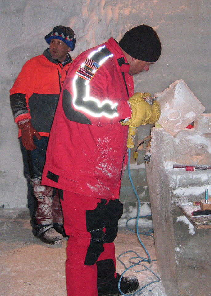Steve Brice, resident ice carver and 15 time world champion ice carver showing student finer techniques on carving a face