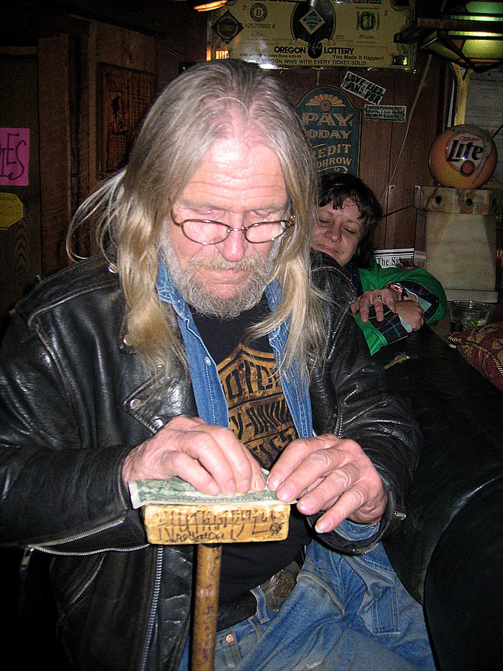 Getting help to put signed dollar on the ceiling of the Yukon Bar, Seward, AK