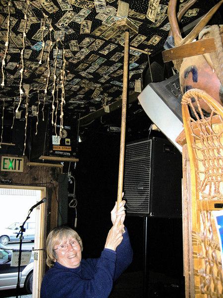 Susan putting dollar on the ceiling of the, Yukon Bar, Seward, AK