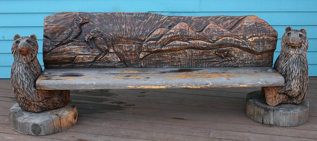 Cute carved wooden bench along wharf at Seward Harbor