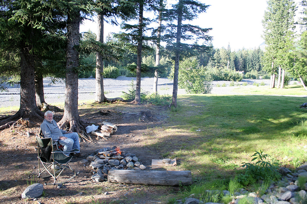 Mike by fire at our campsite with Glacier Creek in background