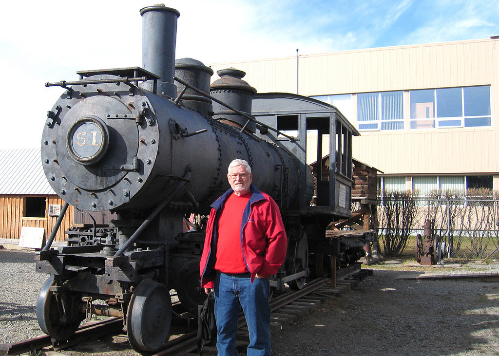 5/18/06 - McBride Museum; Mike in front of Engine 51.  Engine 51 is a wood-fired Books Mogul 2-6-0 built in 1881 in New York and shipped north in 1898 to help build the White Pass and Yukon Railway.  It was rebuilt in 1900 and re-named Engine No. 51.  She operated as a passenger and freight train between Skagway and Whitehorse from 1901 to 1919.  By the 1920's sternwheeler excursions to the Southern Lakes region of the Yukon were very popular.  Part of the trip involved transferring passengers from Tagish Lake overland by rail to Atlin Lake.  The Taku Tramway was nicknamed the World's Shortest Railway.  Engine No. 51 ran this line until 1931 when she returned to service on the WP&YR line and operated as a freight engine until 1941.  During WWII and the construction of the Alaska Highway, the White Pass engines were required to haul heavy loads of supplies and equipment.  Engine No. 51 was replaced by a new and more powerful diesel locomotive.