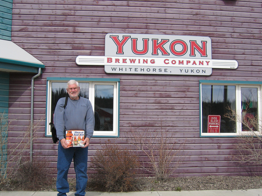 """5/16/06 - Mike in front of the Yukon Brewing Company with his """"Thirst Aid Kit"""", a 12-pack of four of their beers"""