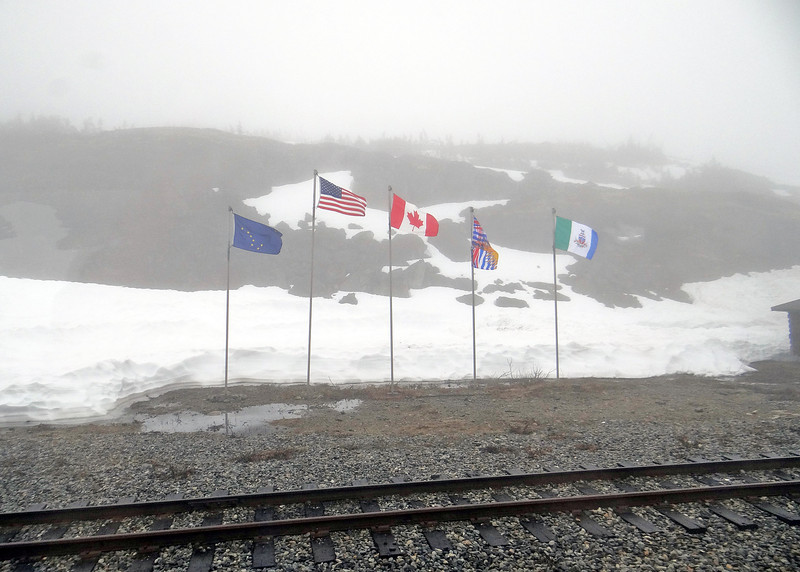 Taken at the White Pass Summit, this is a picture of the flags of the five jurisdictions served by the White Pass & Yukon Route railroad; United States, Alaska, British Columbia, Yukon Territory and Canada.