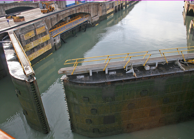 The gate at the Miraflores Lock is beginning to close. <br /> <br /> The heaviest leaves weigh 662 ton; the hinges themselves each weigh 16.7 t (36,817 lb). Each gate has two leaves, 65 ft wide, which close to a V shape with the point upstream; so that the force of water from the higher side pushes the ends of the gates together firmly.