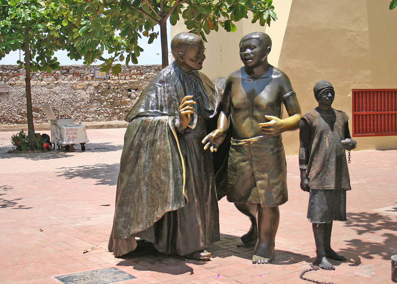 """Claver Plaza - This is a statue of San Pedro Caver and a slave honoring the work and effort of San Pedro Claver in favor of the slaves that came from Africa and sold in Cartegena, an important slaves port at the time.  Just after I took this picture the """"statue"""" on the right stuck his hand out for me to pay him and scared me to death.  The locals find many initiative ways to earn a living but unfortunately I didn't have my purse with me so I didn't have any money."""