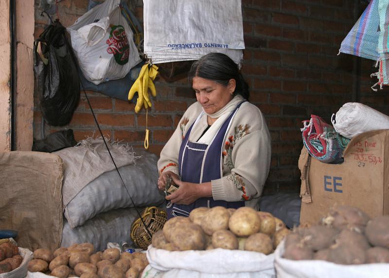 A lady selling potatoes.