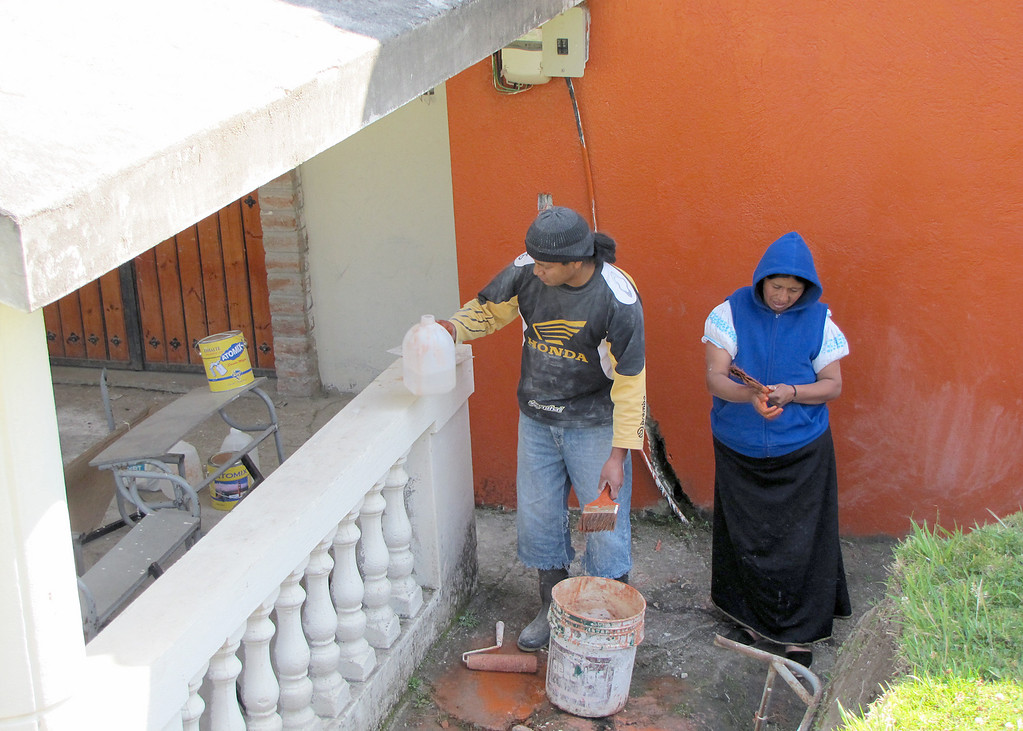 Workers at the Minga painting the building that will be part of the school