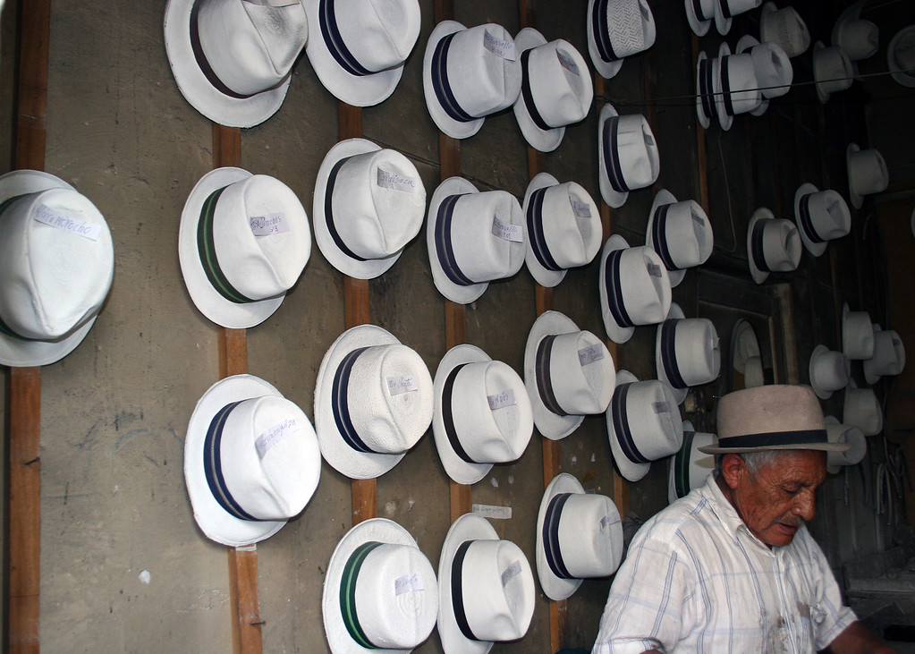 Man in shop working on one of the Panama hats