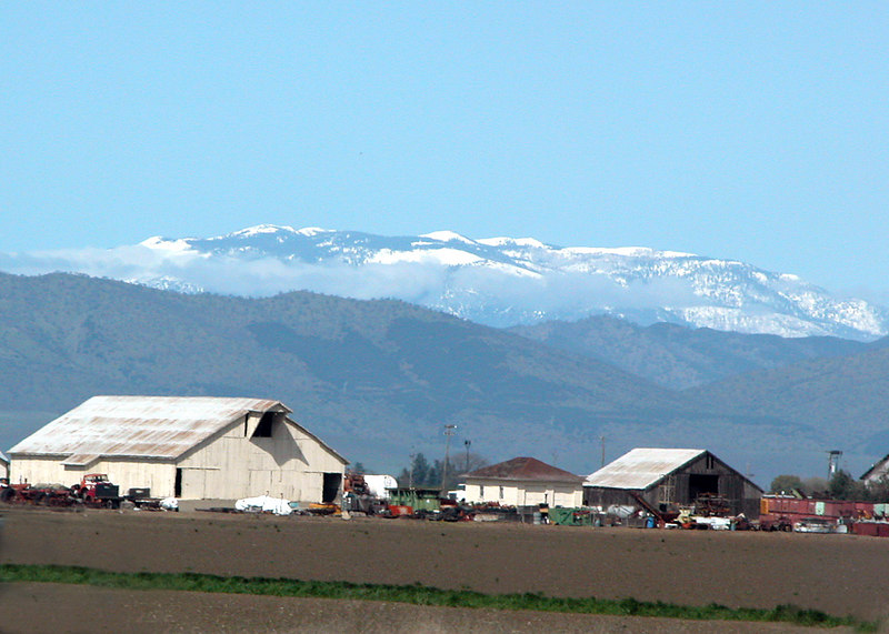 Barn and snow capped mountains in distance