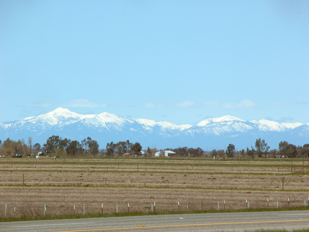 Fields with snow capped mountains in distance