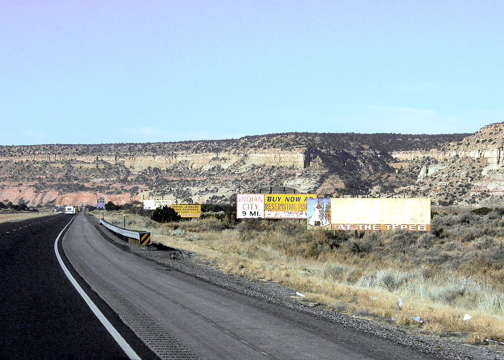 Billboards and cliffs along the road between Gallop, NM and Chambers, AZ